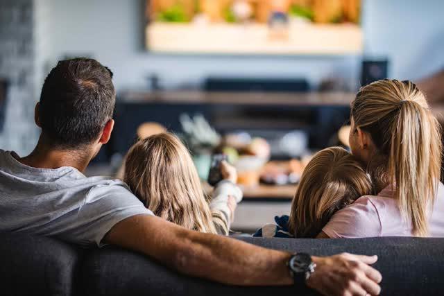 Quatre personnes assises sur un canapé et regardant la télévision